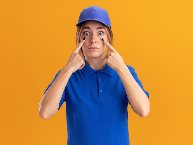 Impressionato giovane ragazza graziosa di consegna in punti uniformi agli occhi con le dita sull'arancio