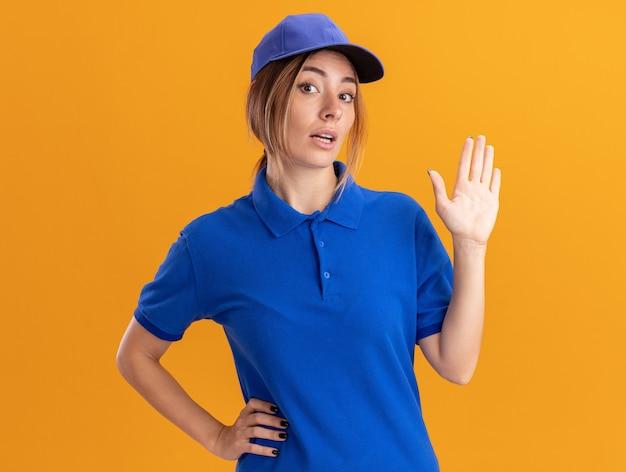 Impressionato giovane bella ragazza di consegna in stand uniforme con la mano alzata sull'arancio
