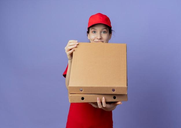 Впечатленная молодая симпатичная доставщица в красной форме и кепке, держащая и открывающую пакеты пиццы, изолированные на фиолетовом фоне с копией пространства