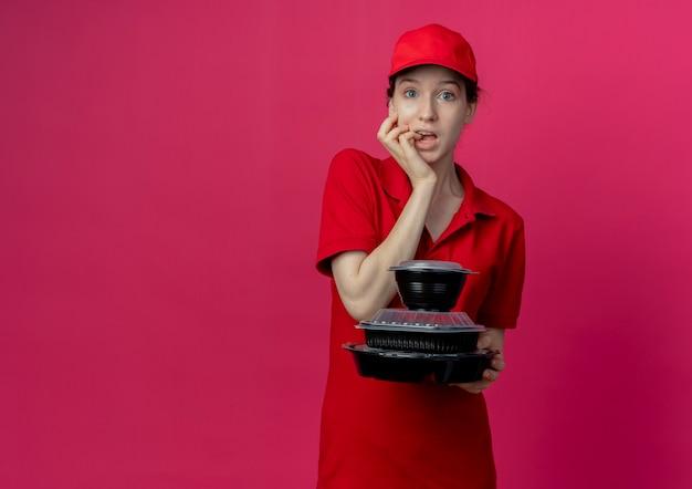 빨간 유니폼과 모자를 쓰고 음식 용기를 들고 복사 공간이 진홍색 배경에 고립 된 그녀의 손가락을 물고 감동적인 젊은 예쁜 배달 소녀