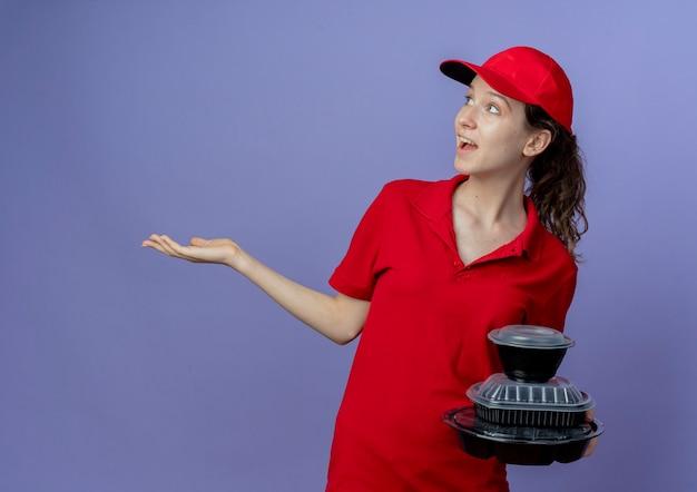 赤い制服を着て、側面を見て、コピースペースで紫色の背景に分離された空の手を示す食品容器を保持しているキャップを身に着けている感動の若いかわいい配達の女の子