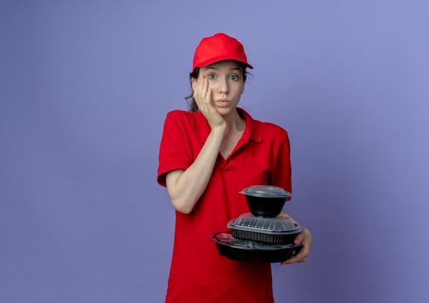赤い制服を着て、コピースペースで紫色の背景に分離された顔に手を置く食品容器を保持しているキャップを身に着けている感動若いかわいい配達