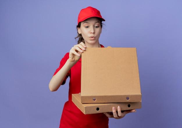 Впечатленная молодая симпатичная курьерская девушка в красной форме и кепке, держащая упаковки с пиццей и заглядывающая внутрь упаковки, изолированной на фиолетовом фоне с копией пространства