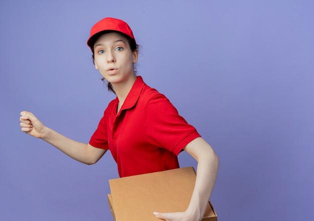 赤いユニフォームとコピースペースで紫色の背景に分離されたくいしばられた握りこぶしで歩くピザパッケージを保持しているキャップを身に着けている感動の若いかわいい配達の女の子