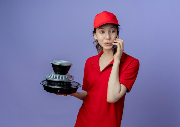 Впечатленная молодая симпатичная курьерская девушка в красной униформе и кепке, смотрящая в сторону, держащую контейнеры с едой, и разговаривающая по телефону, изолированную на фиолетовом фоне с копией пространства