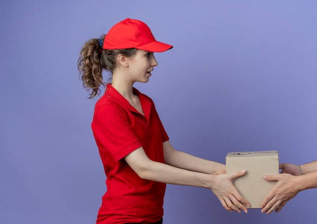 赤い制服とキャップを身に着けている感動の若いかわいい配達の女の子は、コピースペースで紫色の背景に分離されたクライアントにカートンボックスを与える縦断ビューに立っています