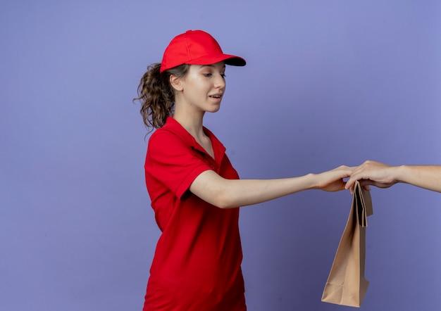 Впечатленная молодая симпатичная курьерская девушка в красной униформе и кепке, стоящая в профиле, раздает бумажный пакет клиенту, изолированному на фиолетовом фоне с копией пространства