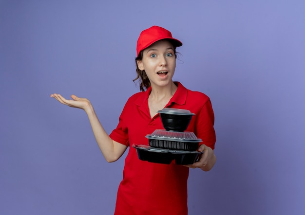 Impressed young pretty delivery girl wearing red uniform and cap holding food containers showing empty hand isolated on purple background with copy space