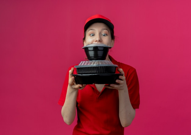 Impressed young pretty delivery girl wearing red uniform and cap holding and looking at food containers isolated on crimson background with copy space