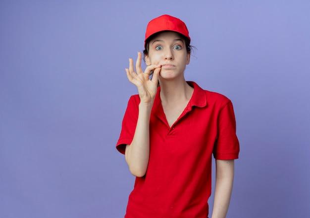 Impressionato giovane bella ragazza di consegna che indossa l'uniforme rossa e berretto che guarda l'obbiettivo zippare la bocca chiusa isolato su sfondo viola con spazio di copia
