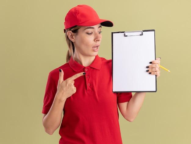 分離された鉛筆を保持しているクリップボードを均一なルックスとポイントで感動した若いかわいい配達の女性
