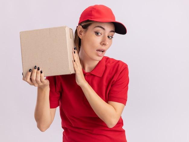 La giovane donna graziosa di consegna impressionata in uniforme tiene il cardbox vicino all'orecchio isolato sulla parete bianca