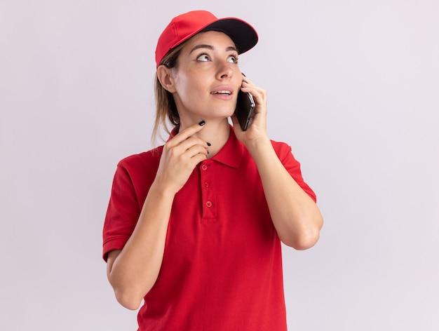 Impressionato giovane donna graziosa di consegna in colloqui uniformi sul telefono e guarda al lato isolato sul muro bianco