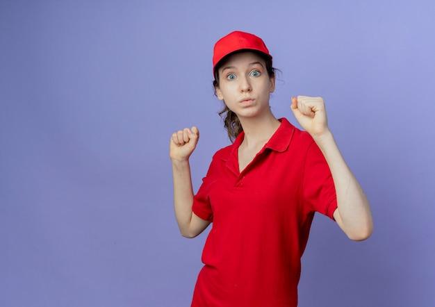 赤い制服とキャップを上げる拳を身に着けている感動の若いかわいい配達の女性