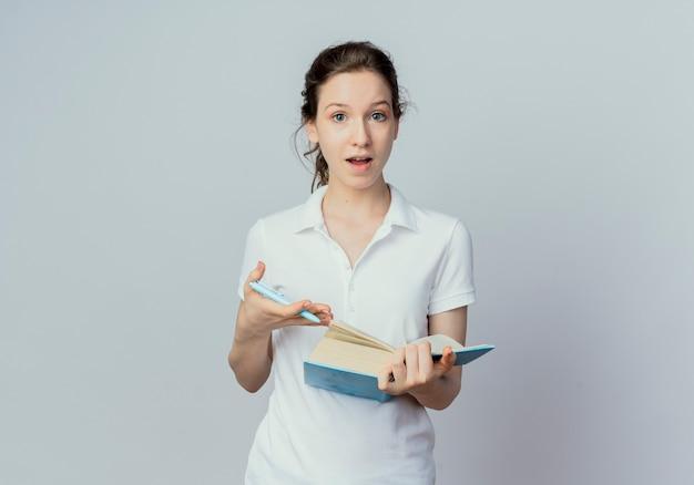 Giovane studentessa graziosa impressionata che tiene libro aperto e penna isolato su priorità bassa bianca con lo spazio della copia