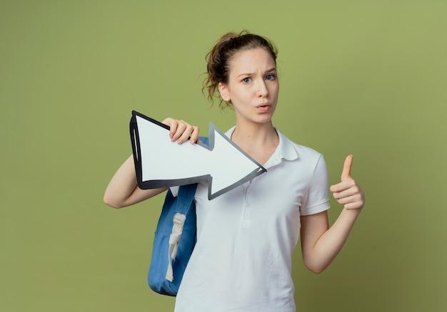 측면을 가리키고 복사 공간이 올리브 녹색 배경에 고립 엄지 손가락을 보여주는 화살표 표시를 들고 다시 가방을 입고 감동 젊은 예쁜 여자 학생