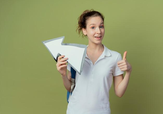 横を指している矢印マークを保持し、コピースペースでオリーブグリーンの背景に分離された親指を示しているバックバッグを身に着けている印象的な若いきれいな女性の学生