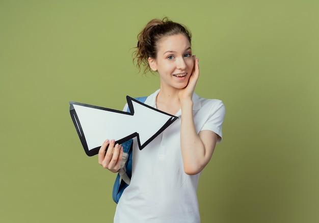 Впечатленная молодая симпатичная студентка в задней сумке, держащая стрелку, указывающую в сторону и трогательное лицо, изолированную на оливково-зеленом фоне с копией пространства