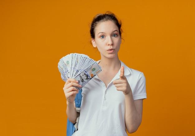 Впечатленная молодая симпатичная студентка в задней сумке, держащая деньги и указывающая на камеру, изолированную на оранжевом фоне с копией пространства