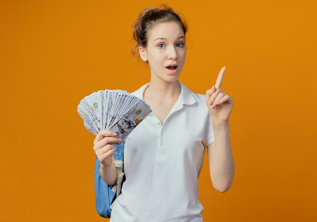 Impressionato giovane studentessa graziosa che indossa la borsa posteriore tenendo i soldi e alzando il dito isolato su sfondo arancione con copia spazio