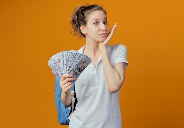 Impressionato giovane studentessa graziosa che indossa la borsa posteriore tenendo i soldi toccando il mento isolato su sfondo arancione con copia spazio