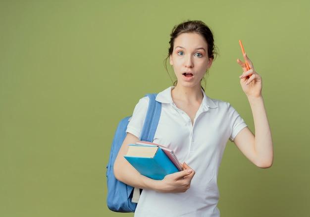 Впечатленная молодая симпатичная студентка в задней сумке, держащая блокнот и книгу, поднимающая ручку, изолированную на оливково-зеленом фоне с копией пространства