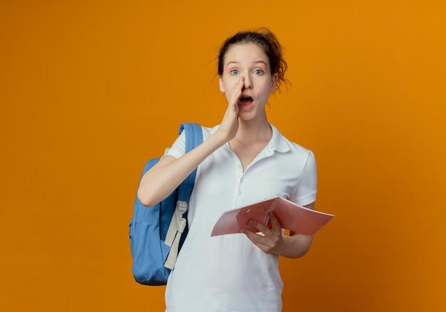 Impressionato giovane studentessa graziosa che indossa la borsa posteriore che tiene il blocco note aperto e sussurra qualcosa alla macchina fotografica con la mano vicino alla bocca isolata su fondo arancio con lo spazio della copia