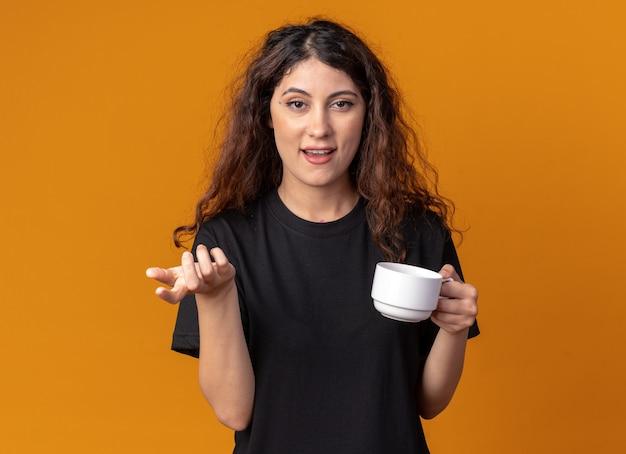 Impressionato giovane bella ragazza che tiene una tazza di tè guardando e puntando la telecamera
