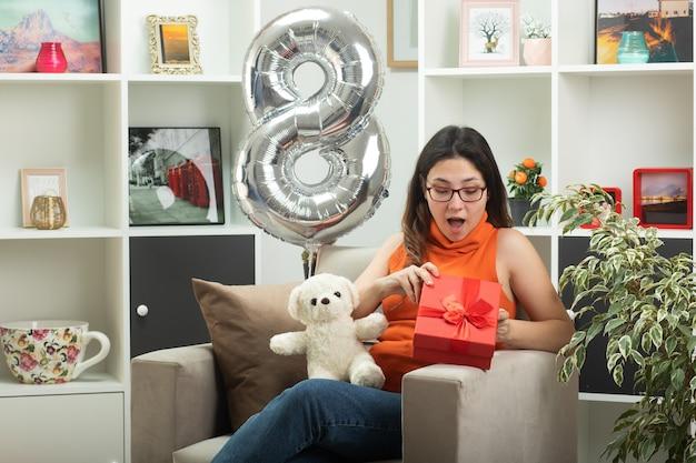 Впечатленная молодая красивая девушка в оптических очках открывает и смотрит на подарочную коробку, сидя на кресле в гостиной в международный женский день в марте