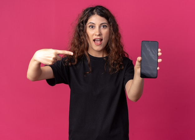 그것을 가리키는 카메라에 휴대 전화를 보여주는 감동 어린 예쁜 여자