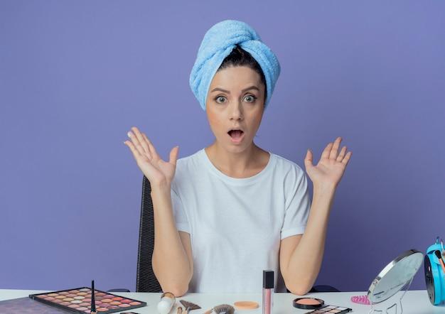 紫色の背景で隔離の空の手を示す化粧ツールと頭の上のバスタオルで化粧テーブルに座っている感動の若いかわいい女の子