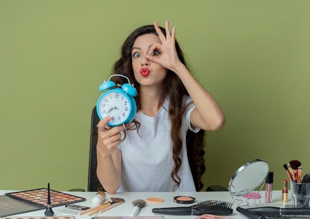 Впечатленная молодая красивая девушка сидит за косметическим столом с инструментами для макияжа, держит будильник и делает жест взгляда в камеру, изолированную на оливково-зеленом фоне