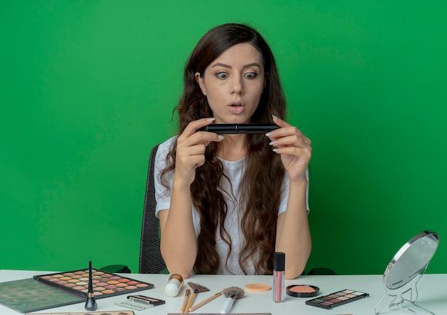 메이크업 도구를 들고 녹색 배경에 고립 된 마스카라를보고 메이크업 테이블에 앉아 감동 젊은 예쁜 여자