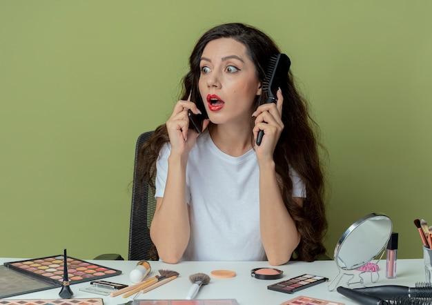 印象的な若いかわいい女の子は、櫛を保持し、オリーブグリーンの背景で隔離の櫛で頭に触れる側を見て電話で話している化粧ツールで化粧テーブルに座っています。