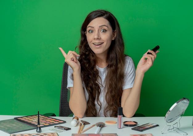 마스카라를 들고 녹색 배경에 고립 된 손가락을 올리는 메이크업 도구로 메이크업 테이블에 앉아 감동 젊은 예쁜 여자