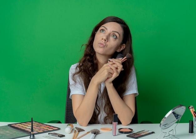 緑の背景に分離された見上げるパウダーと赤面ブラシを保持している化粧ツールで化粧テーブルに座っている感動の若いかわいい女の子