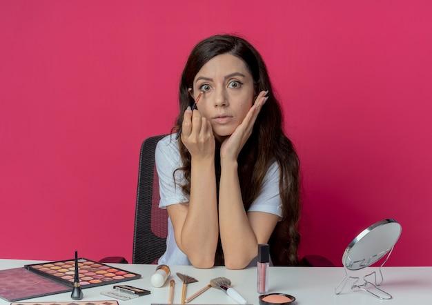 Впечатленная молодая красивая девушка сидит за косметическим столом с инструментами для макияжа, кладет руку на лицо и наносит тени для век кистью, изолированной на малиновом фоне