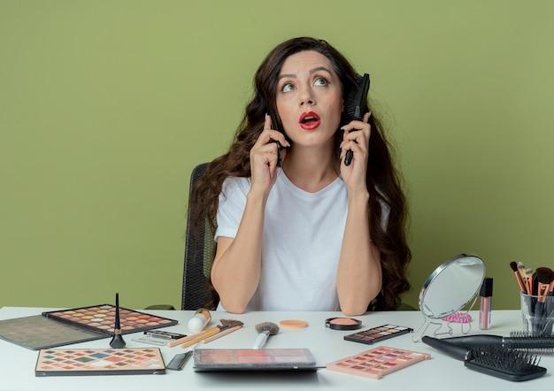 横を見て、オリーブグリーンの背景で隔離の電話で話している櫛で頭に触れる化粧ツールで化粧テーブルに座っている感動の若いかわいい女の子