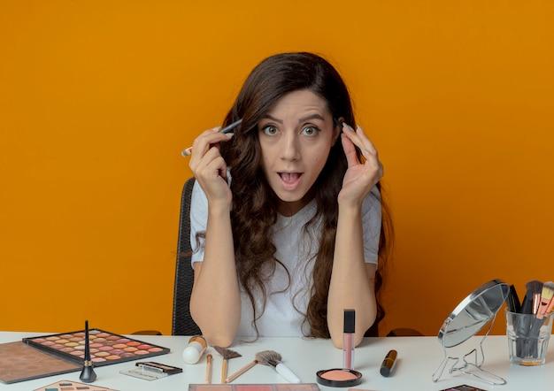 Впечатленная молодая красивая девушка сидит за макияжным столом с инструментами для макияжа, касаясь висков кистями для макияжа