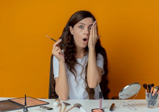 Impressionato giovane bella ragazza seduta al tavolo per il trucco con strumenti per il trucco che copre metà del viso con la mano e tenendo il pennello ombretto isolato su sfondo arancione