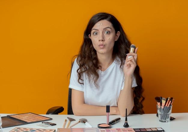 Impressionato giovane bella ragazza seduta al tavolo da trucco con strumenti di trucco tenendo il pennello per fondotinta con crema per fondotinta messo sul suo viso isolato su sfondo arancione
