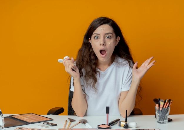Impressionato giovane bella ragazza seduta al tavolo per il trucco con strumenti di trucco che tiene la crema di fondazione e mostrando la mano vuota con la crema di fondazione messa sul viso isolato su sfondo arancione