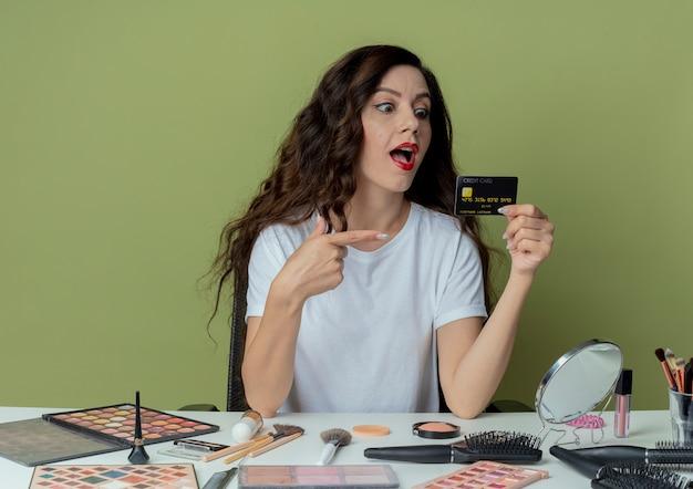 Impressionata giovane bella ragazza seduta al tavolo da trucco con strumenti per il trucco che tengono guardando e puntando la carta di credito su uno spazio verde oliva