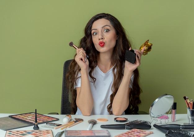 Impressionato giovane bella ragazza seduta al tavolo per il trucco con strumenti per il trucco che tiene la spazzola della polvere e la tazza del vincitore e gesticolando bacio alla macchina fotografica isolata su fondo verde oliva