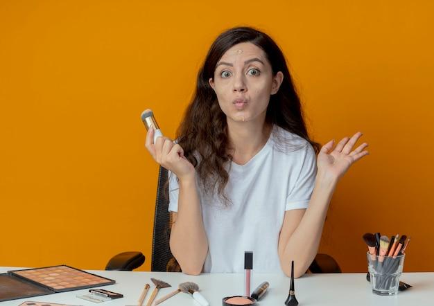 Impressionato giovane bella ragazza seduta al tavolo per il trucco con strumenti di trucco tenendo la mano in aria e tenendo il pennello per fondotinta con crema per fondotinta messo sul viso isolato su sfondo arancione