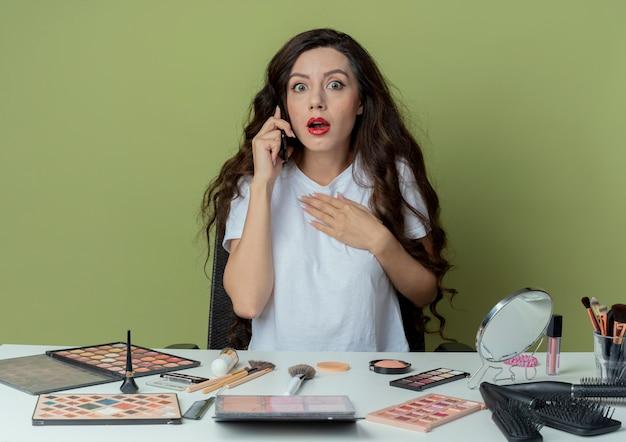 Impressionato giovane bella ragazza seduta al tavolo da trucco con strumenti di trucco parlando al telefono mettendo la mano sul petto isolato su sfondo verde oliva