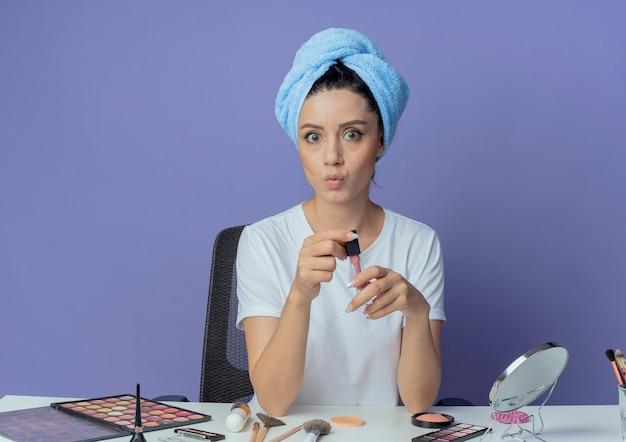 Impressionata giovane bella ragazza seduta al tavolo da trucco con strumenti per il trucco e con asciugamano da bagno sulla testa che tiene lucidalabbra