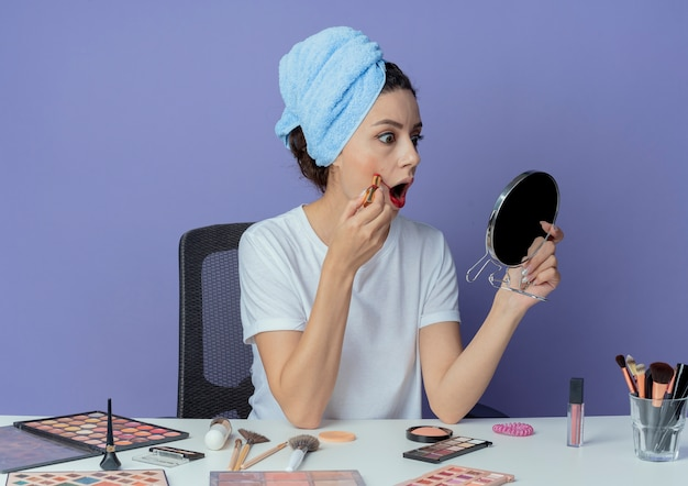 Impressed young pretty girl sitting at makeup table with makeup tools and with bath towel on head holding and looking at mirror and putting on red lipstick on cheek isolated on purple background