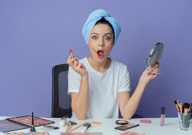 Impressed young pretty girl sitting at makeup table with makeup tools and with bath towel on head holding mirror and holding red lipstick isolated on purple background