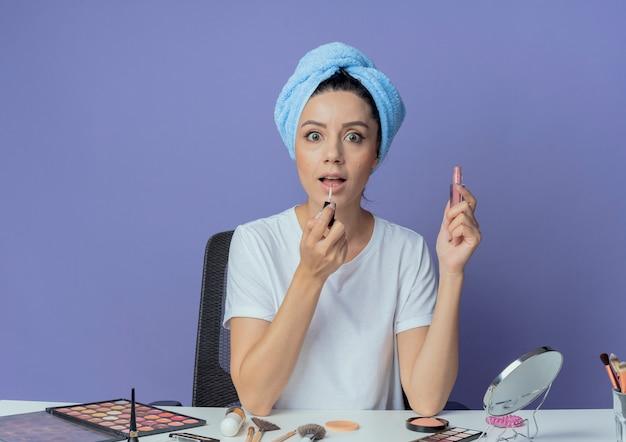 Impressionato giovane bella ragazza seduta al tavolo per il trucco con strumenti per il trucco e con asciugamano da bagno sulla testa mettendo su lucidalabbra isolato su sfondo viola